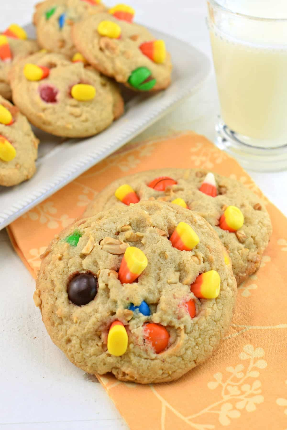 Pay Day cookies with peanuts, m&M's and candy corn, stacked on a light orange linen.