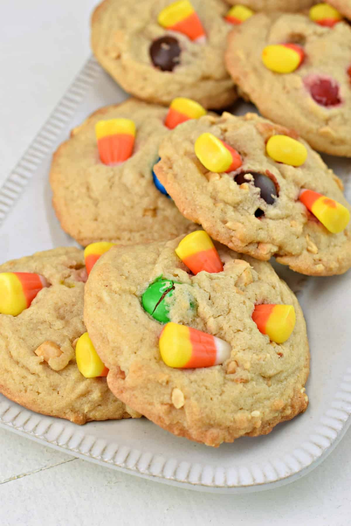 Pay day cookies with candy corn on a white rectangle plate.