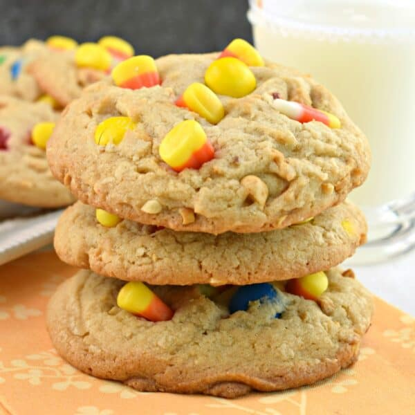Stack of three peanut butter cookies with candy corn, peanuts, and M&M'S.