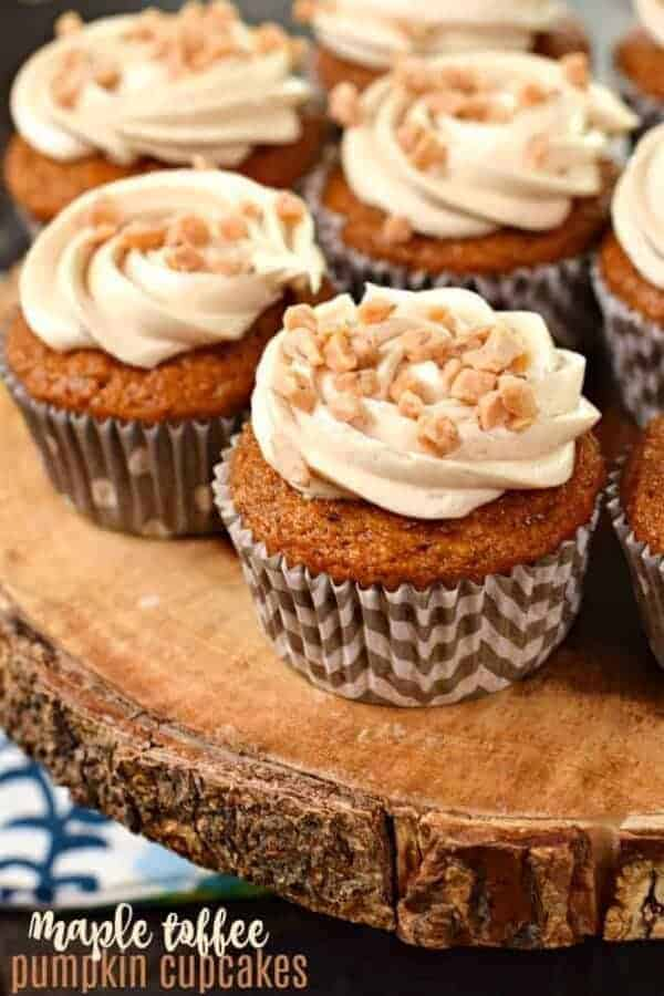 Pumpkin cupcakes on wooden cake tray with maple toffee frosting swirled on top.