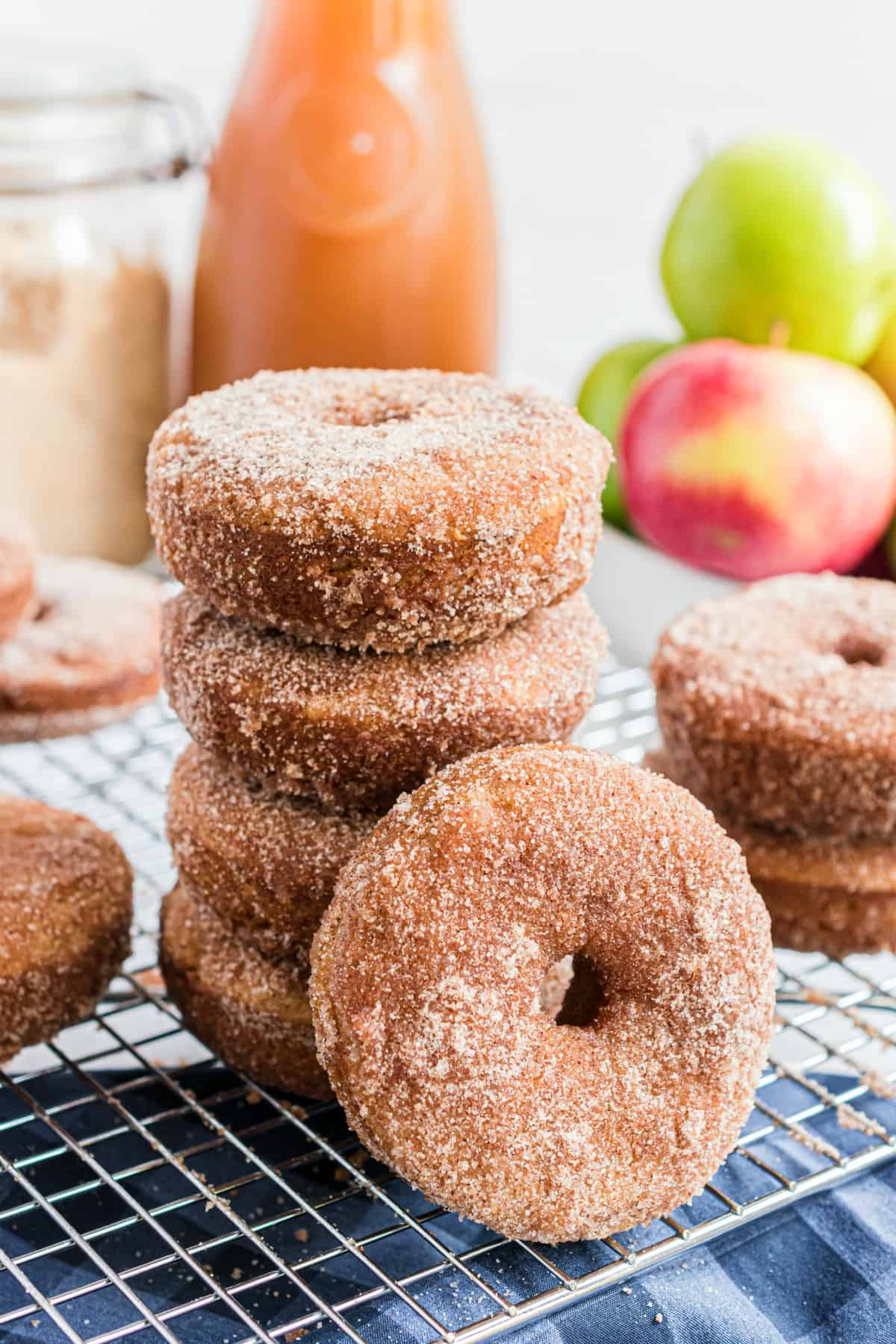 Stack of apple cider donuts on a wire rack with one tilted sideways.