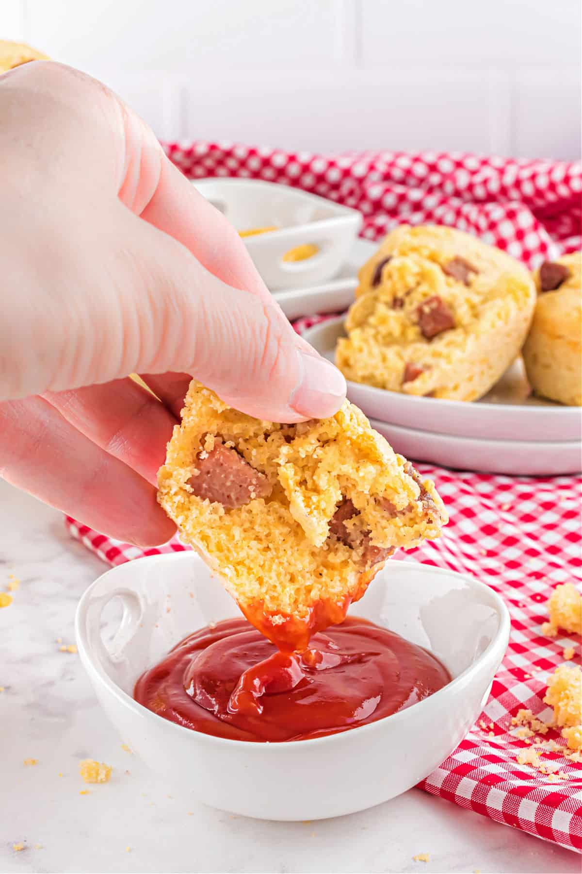 Half a corn dog muffin being dipped into a white bowl with ketchup.