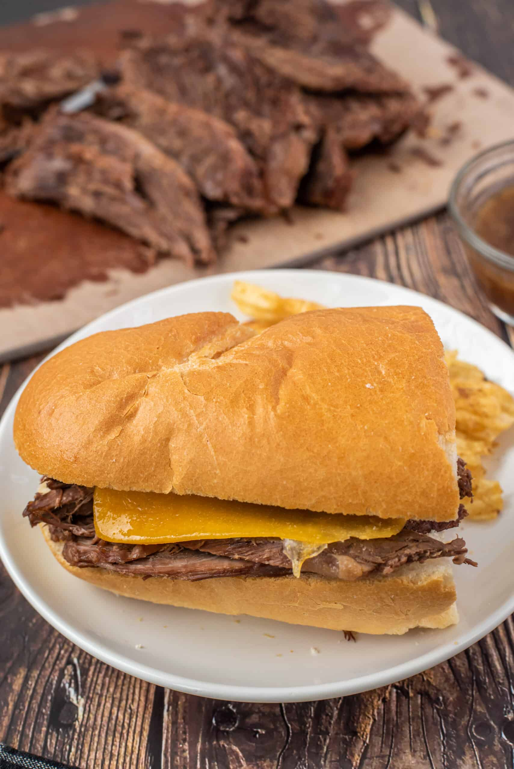 French Dip sandwich on baguette with sliced beef in background.