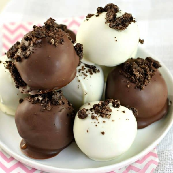 Close up photo of dark chocolate and white chocolate oreo peanut butter truffles with cookie crumbs