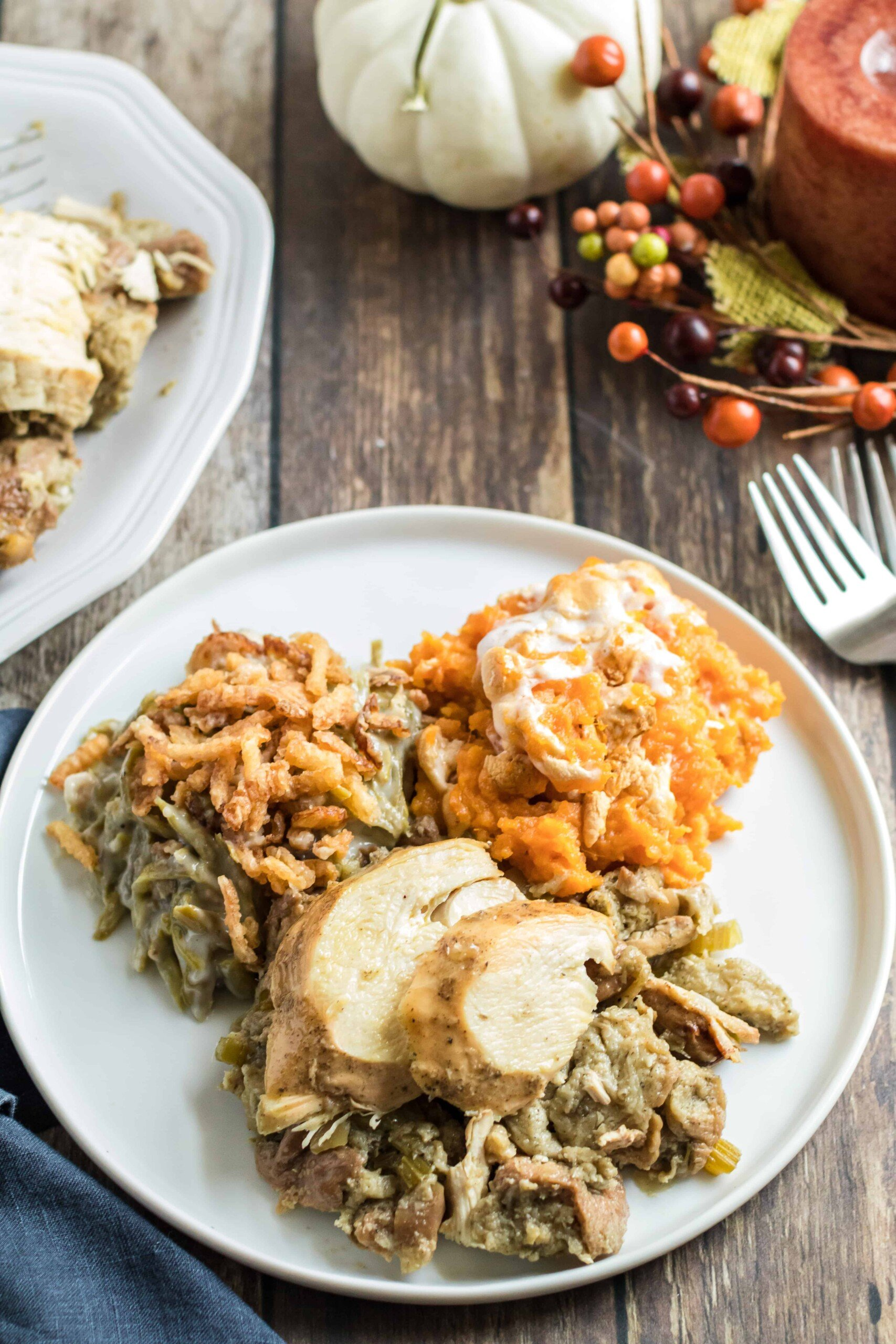 Dinner plate with a scoop of turkey and stuffing with sweet potato casserole and green bean casserole.