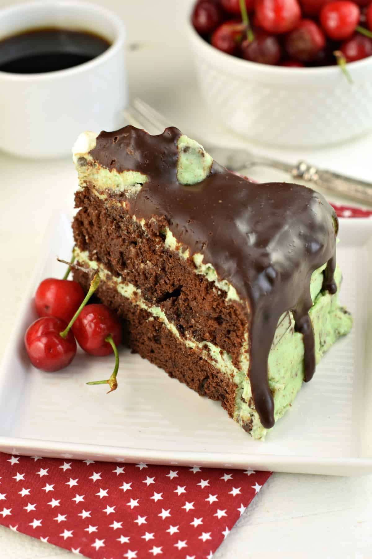 Thick slice of chocolate layer cake with mint chocolate chip frosting tinted green and covered in chocolate ganache. Served on a white square dessert plate with fresh cherries.