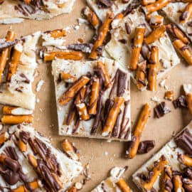 Pieces of white chocolate candy with salted caramel, pretzels, and milk chocolate drizzled on top.