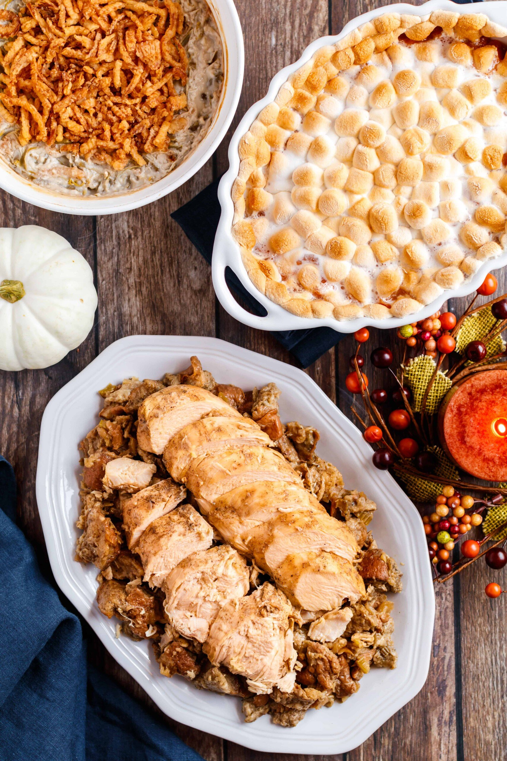 Plate of stuffing topped with sliced turkey breast on a thanksgiving table.