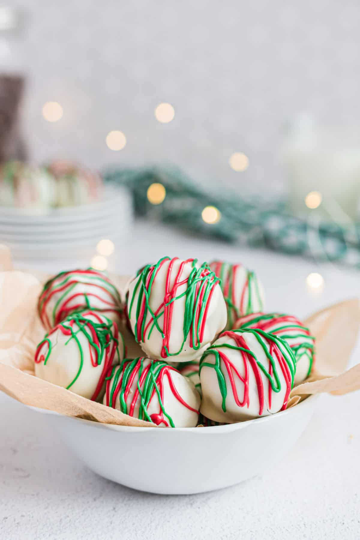 Almond truffles in white bowl with christmas lights in background.
