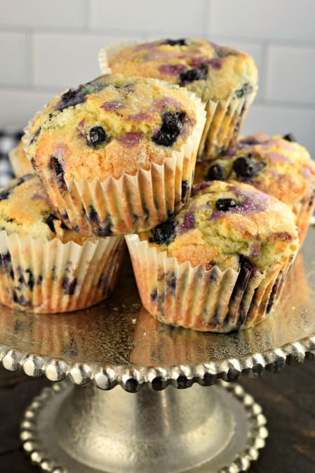 Blueberry muffins stacked on a beaded silver cake platter.