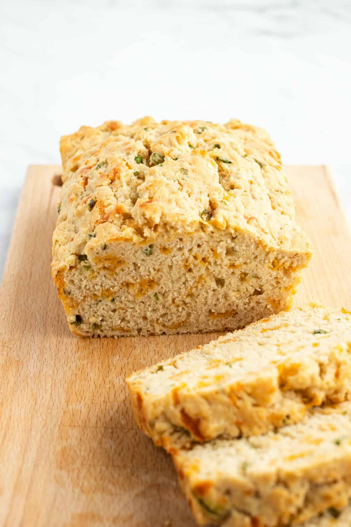 Beer bread with cheese and green onions on a wooden cutting board with several slices cut.