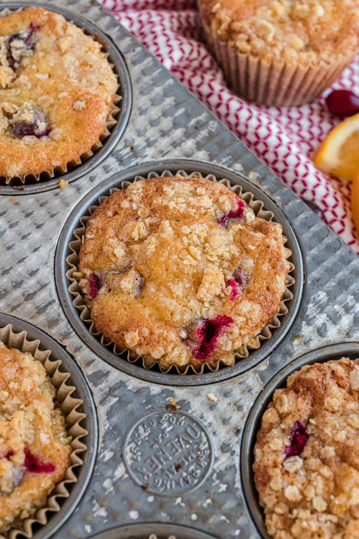 Cranberry orange muffins in a muffin pan with streusel.