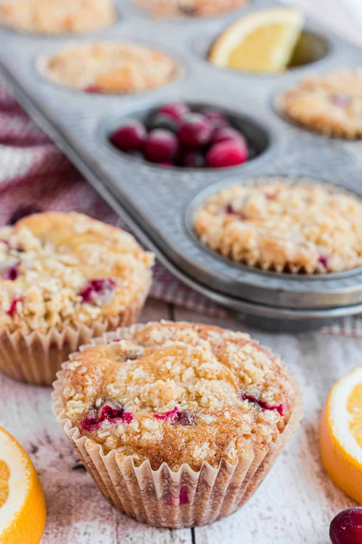 Cranberry orange muffins on counter with muffin pan in background.