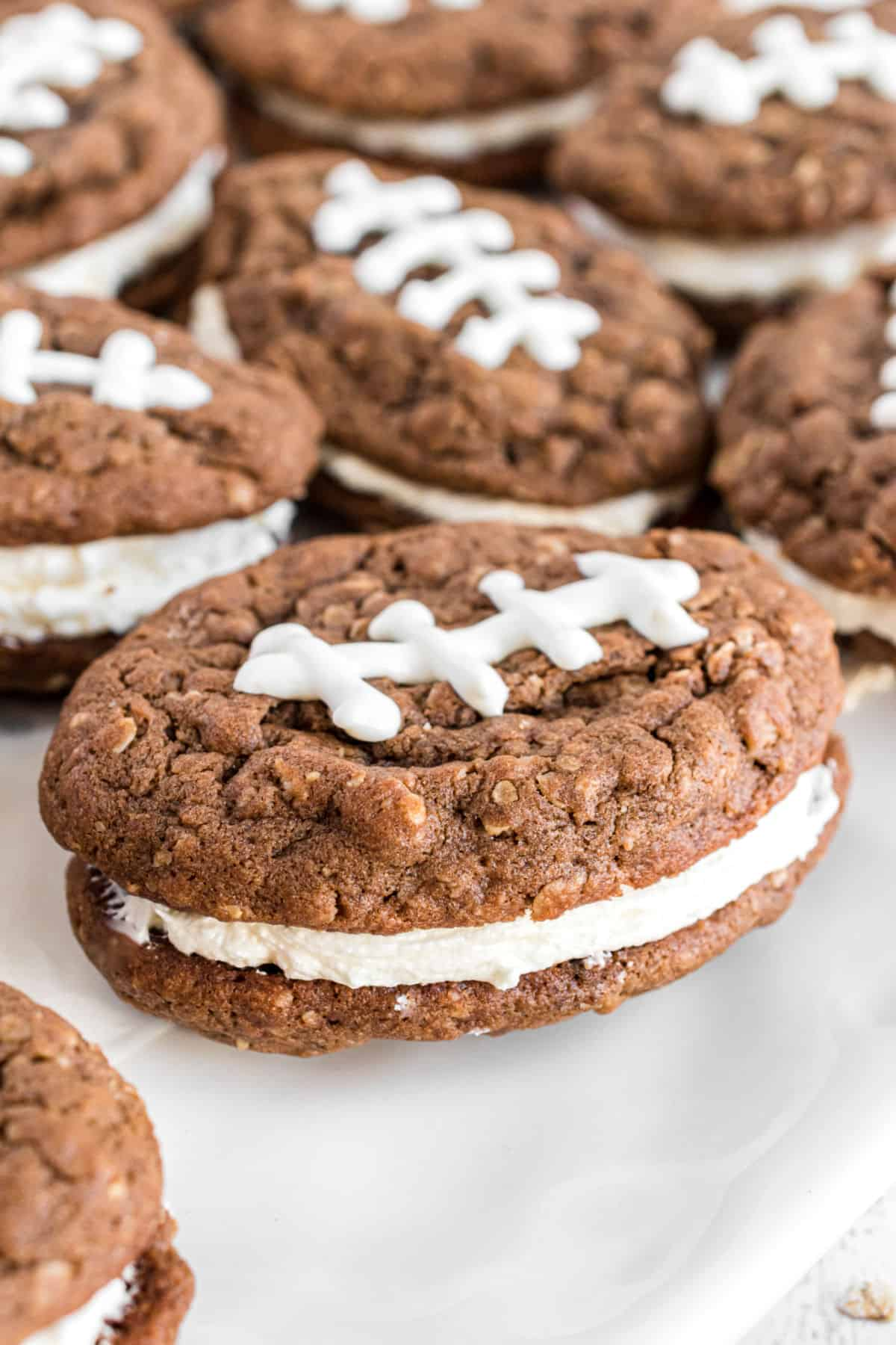 Football shaped oatmeal cream pies on white cake platter.