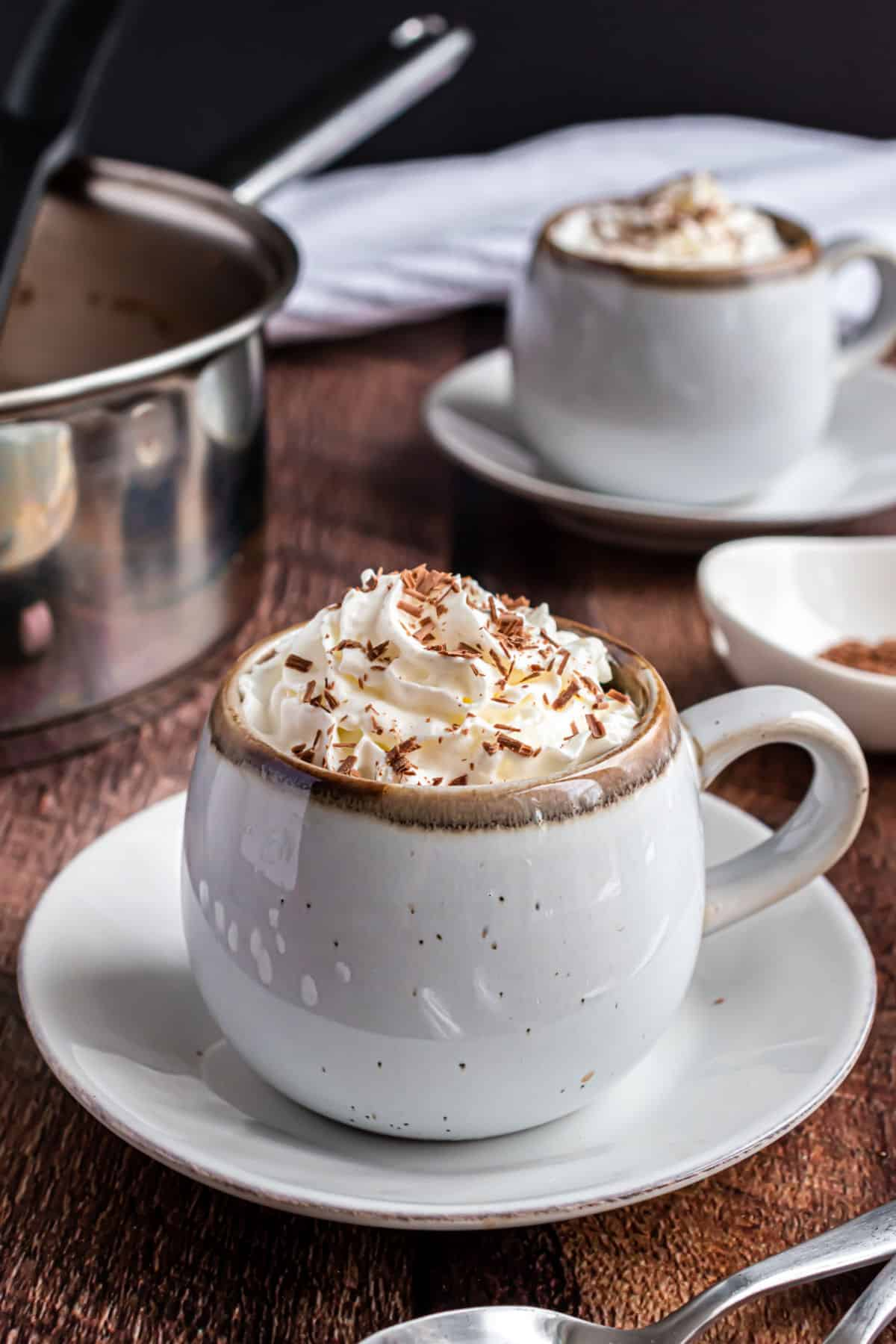 Hot chocolate with whipped cream in a ceramic white mug.