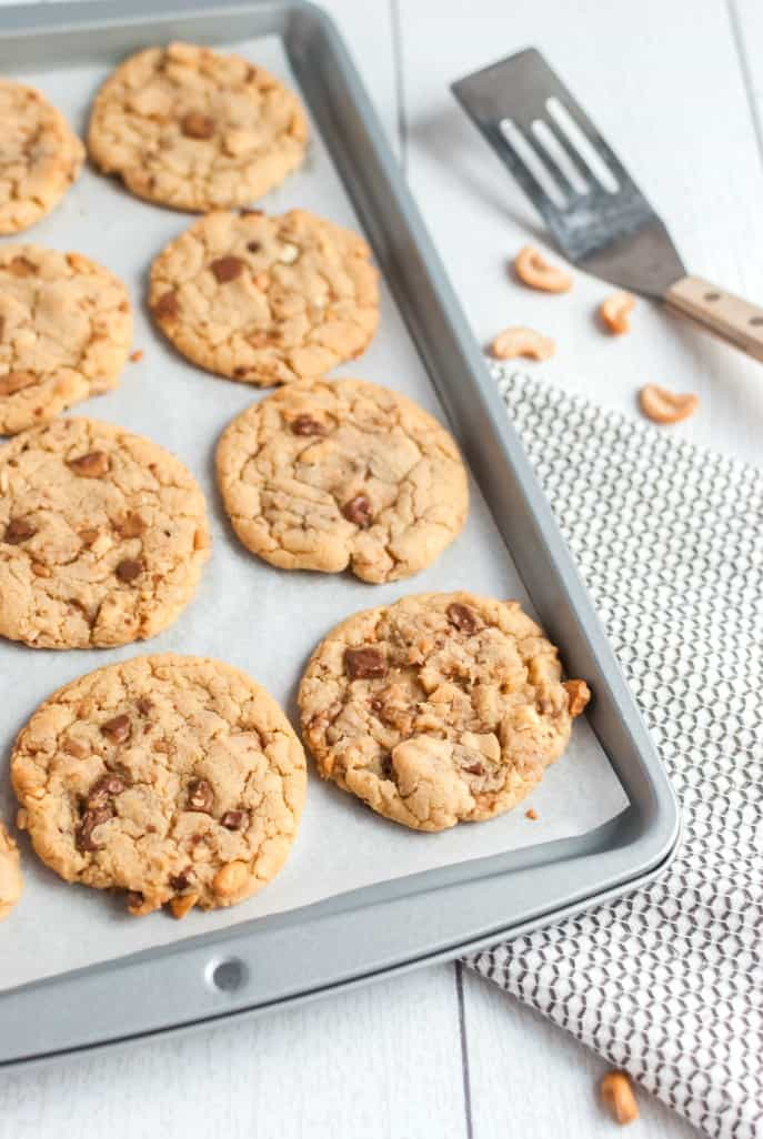 Cookies on a baking sheet with cashews.