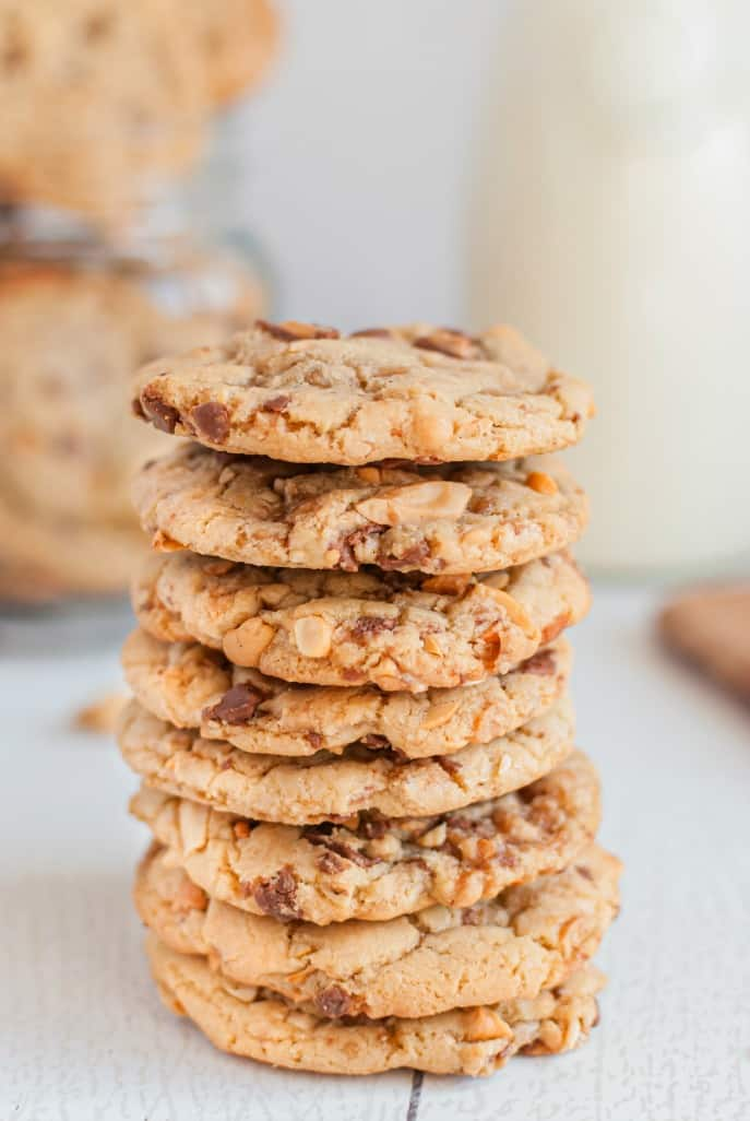 Tall stack of toffee cashew cookies on a wooden surface.