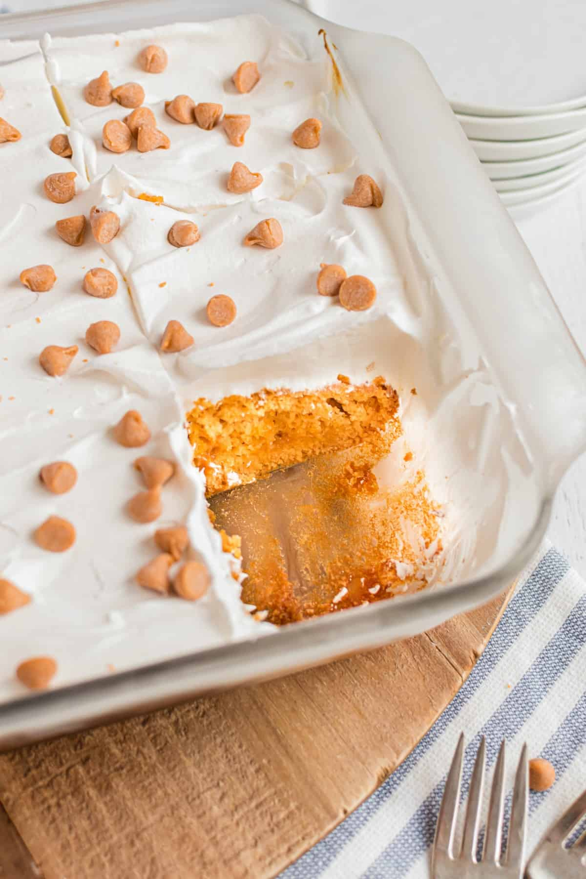 Glass 13x9 baking dish with a butterscotch pudding cake topped with cool whip, and one slice removed from the pan.