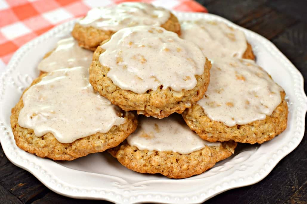 White plate piled up with iced oatmeal cookies.