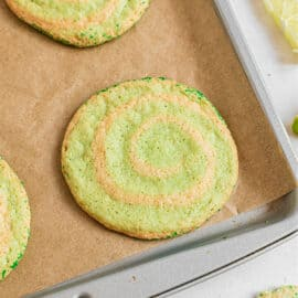 Lime swirled icebox cookies with green sprinkles on a parchment paper lined cookie sheet.