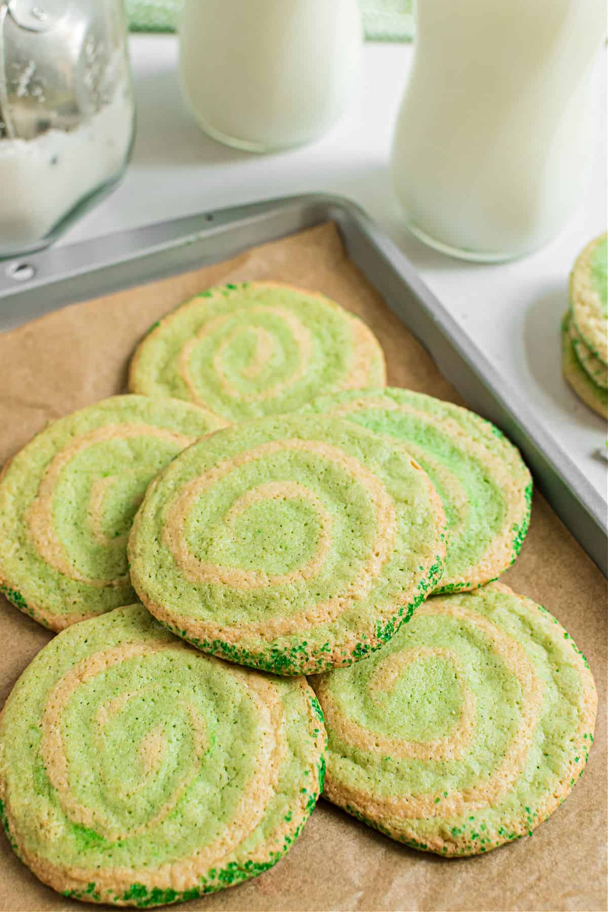 Stack of baked icebox swirled cookies on a parchment paper lined baking sheet.