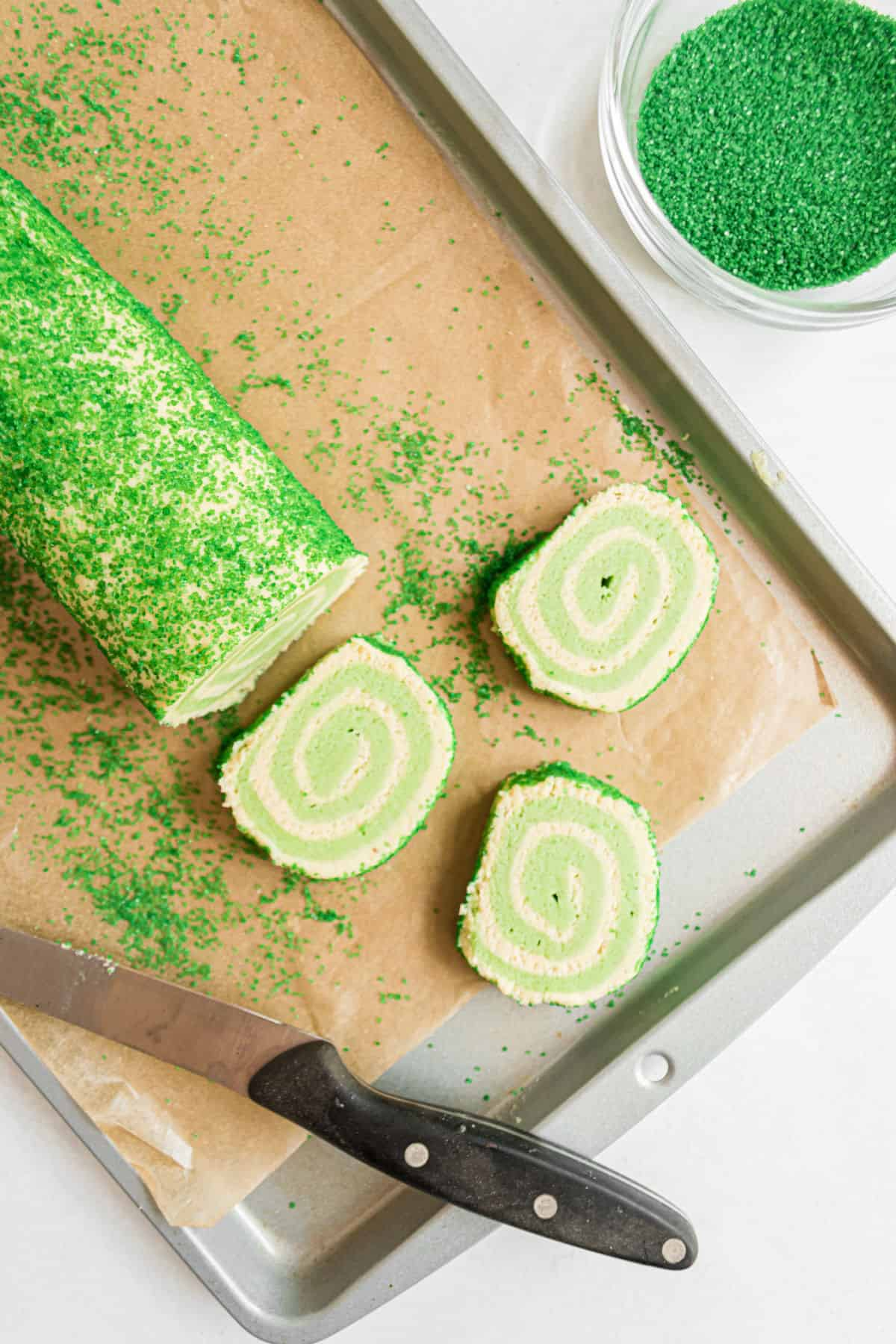 Slices of icebox cookies with lime swirls on parchment paper.