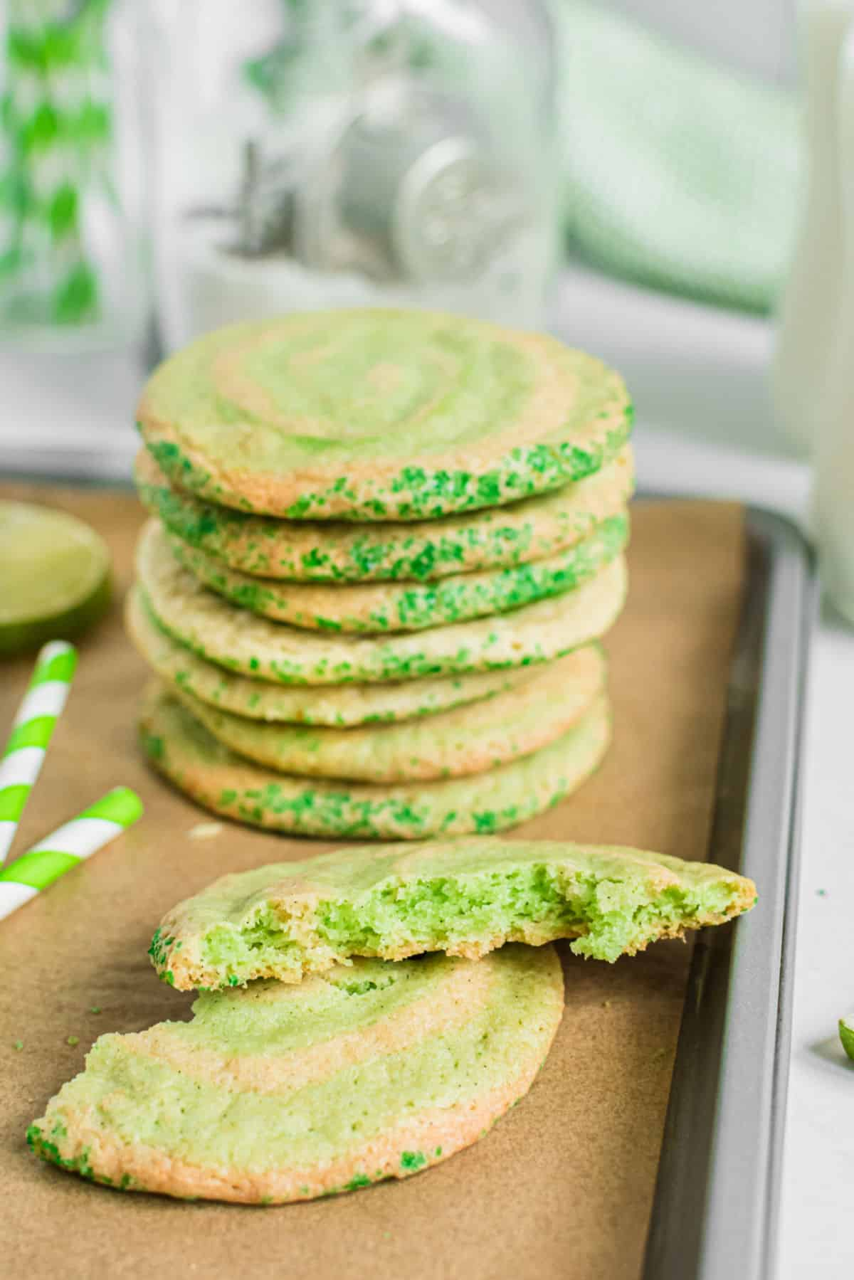 Stack of lime swirled icebox cookies on cookie sheet with one cookie broken in half.