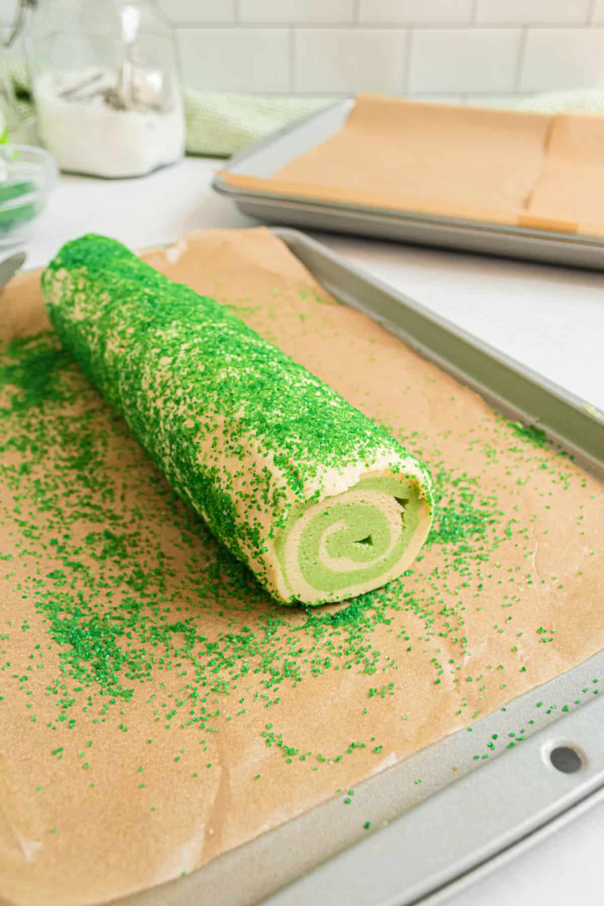 Lime swirled icebox cookies on parchment paper being rolled in sprinkles.