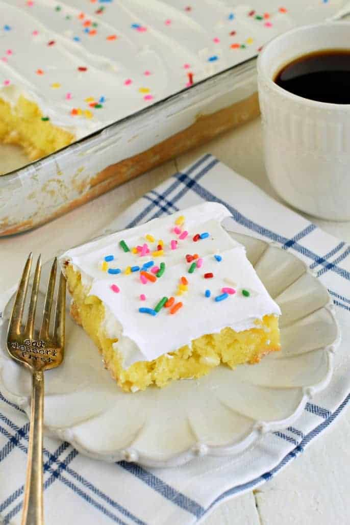 Lemon pudding cake with whipped cream and sprinkles.