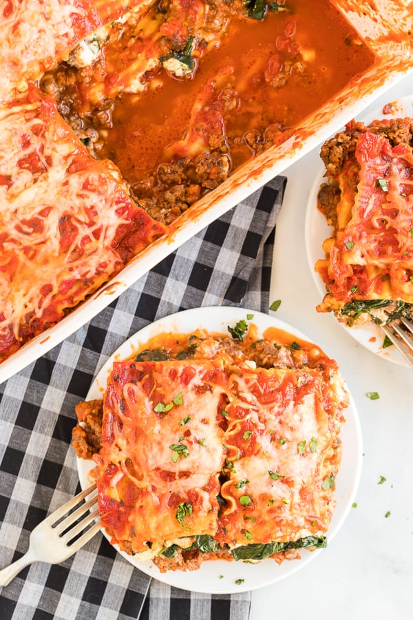 Overhead view of spinach and meat lasagna being served on two white dinner plates.