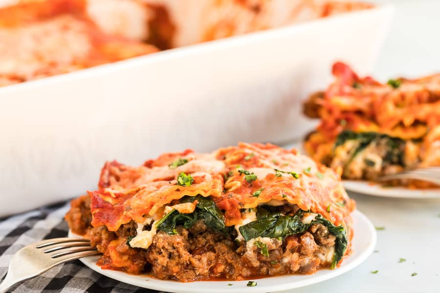 Slice of spinach and meat lasagna on a white dinner plate.