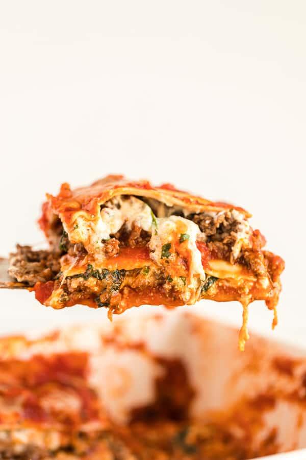 Spatula lifting a slice of cheesy, saucy lasagna out of baking dish.