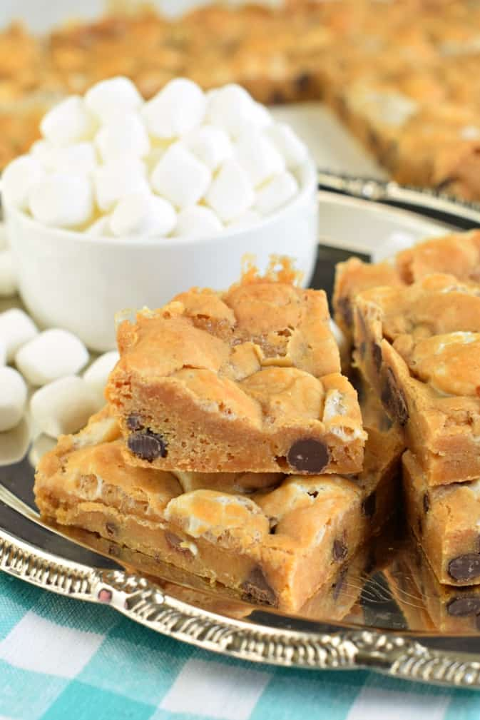 Stack of butterscotch marshmallow bars on silver plate with bowl of mini marshmallows.
