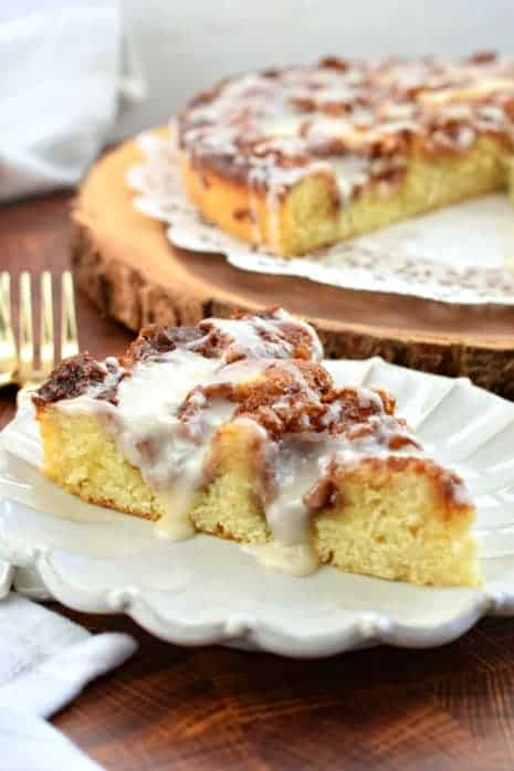 Slice of Cinnabon Cinnamon Roll cake with dripping vanilla glaze on white scalloped plate.