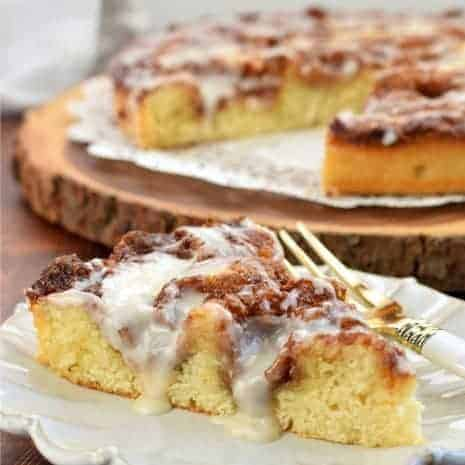 Slice of cinnamon roll cake on a white plate with whole cake in background.