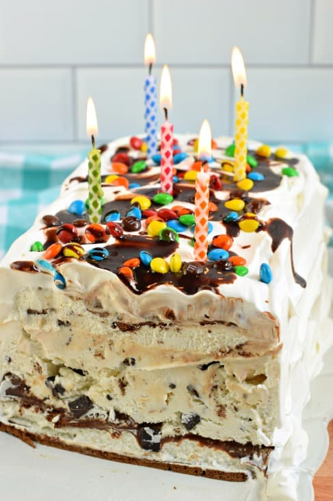 Ice cream cake with layers showing and topped with lit candles.
