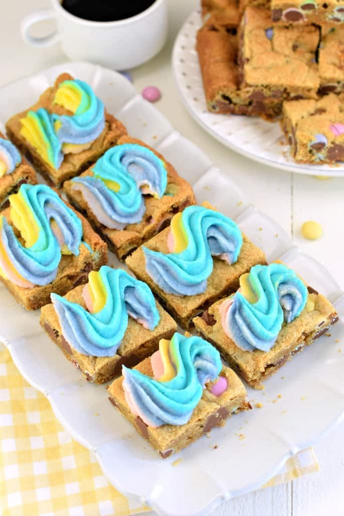 Plate of square cute rainbow frosted chocolate chip cookies bars with a plate of plain (non frosted) bars in the back ground.