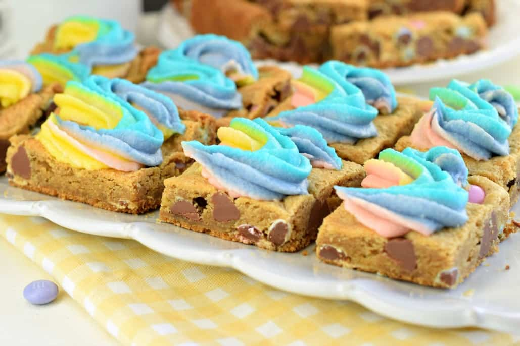 White scalloped plate with squares of rainbow frosted cookie bars.