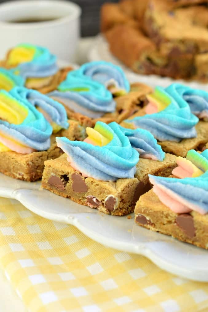 Chocolate Chip cookie bars with rainbow swirled frosting on a white plate with yellow napkin underneath.