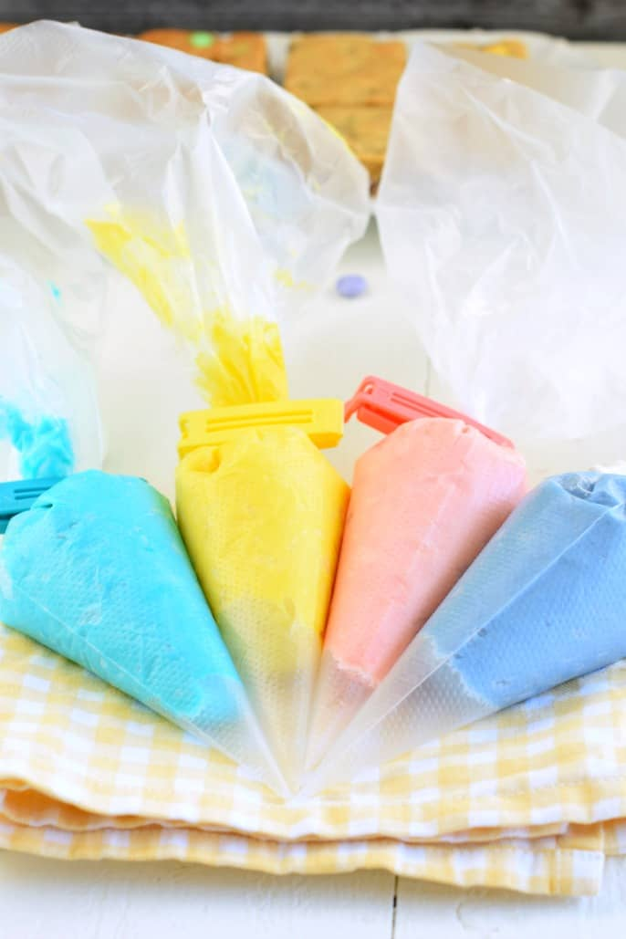 4 clear decorator bag with the colored frosting...blue, yellow, pink, purple.