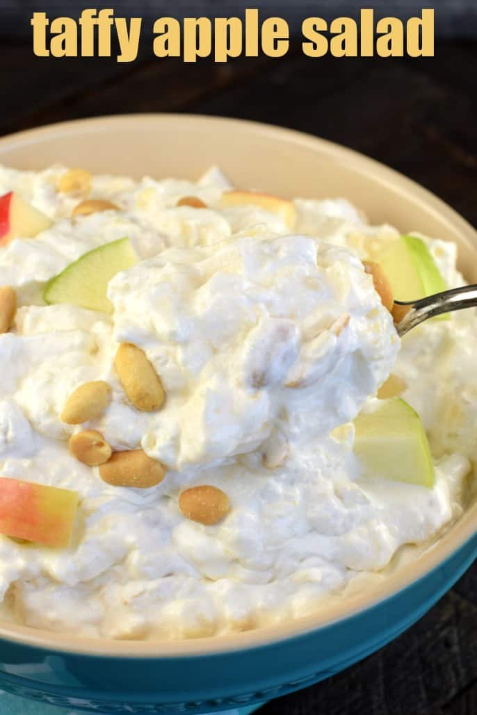 Spoonful of taffy apple salad being scooped out of blue bowl.