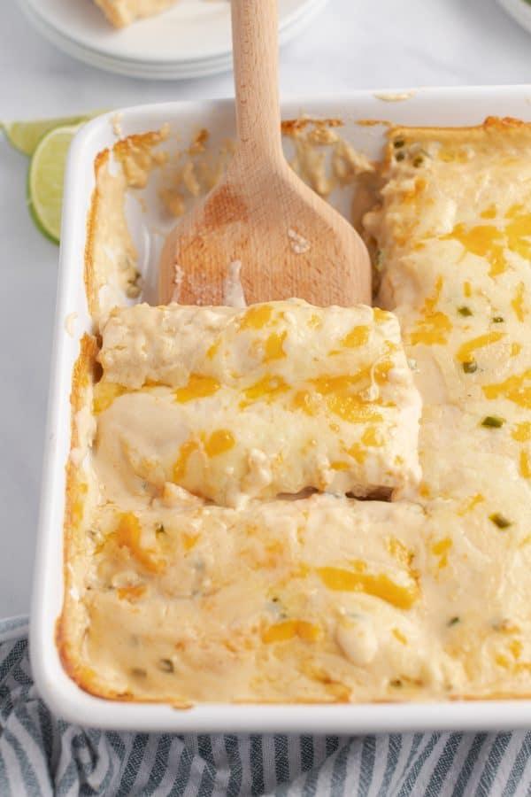 Pan of cream chicken enchiladas with wood spatula