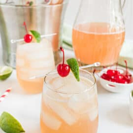 Cherry margaritas in a glass garnished with lime and maraschino cherries.