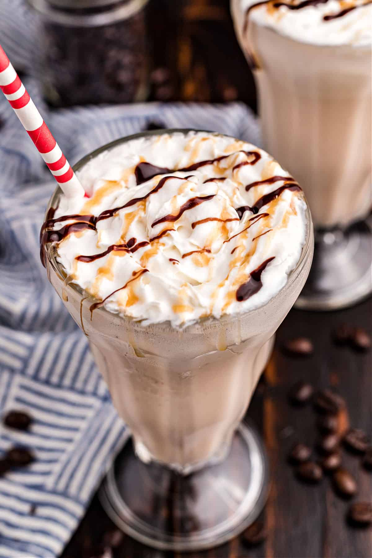 Coffee milkshake in a glass with caramel and chocolate drizzled on top.