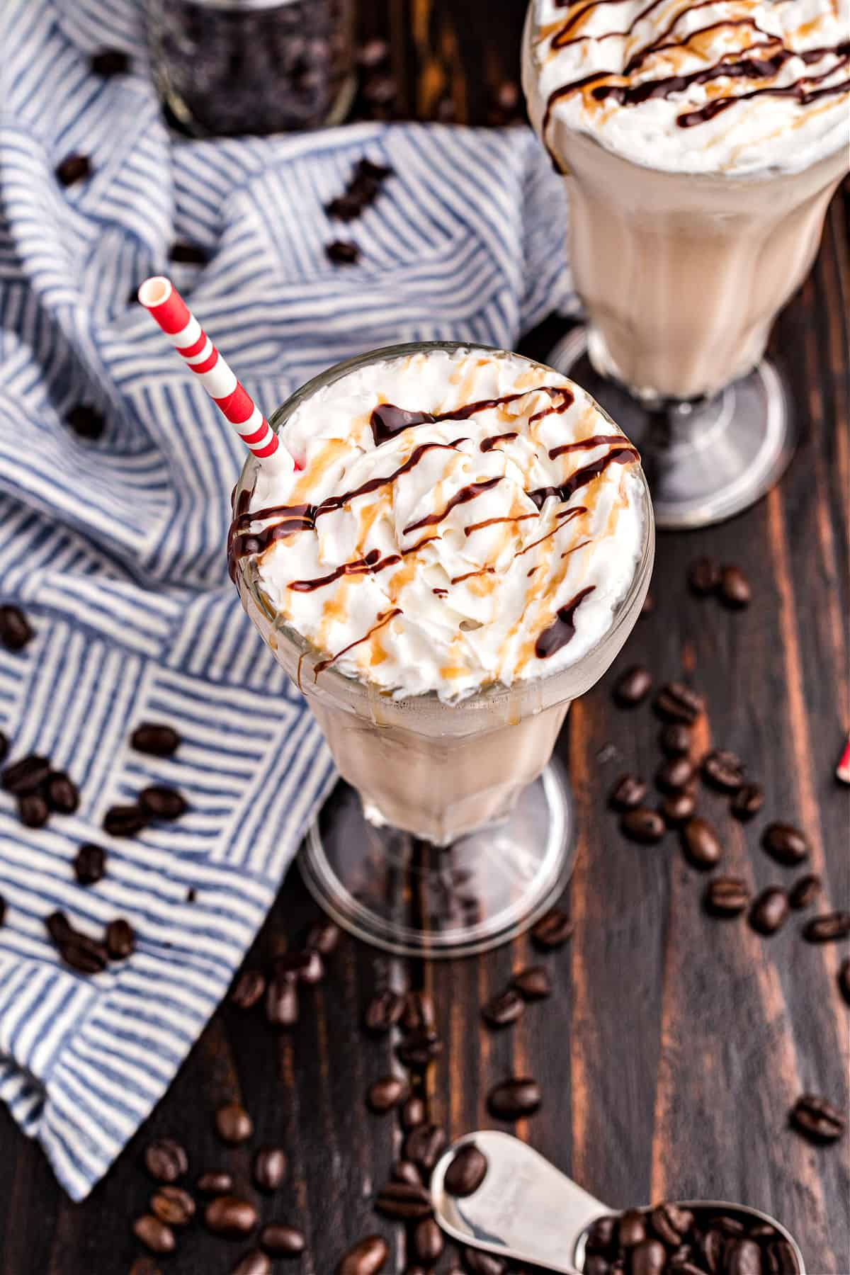 Two tall glasses of coffee milkshakes topped with drizzles of caramel and chocolate sauce.
