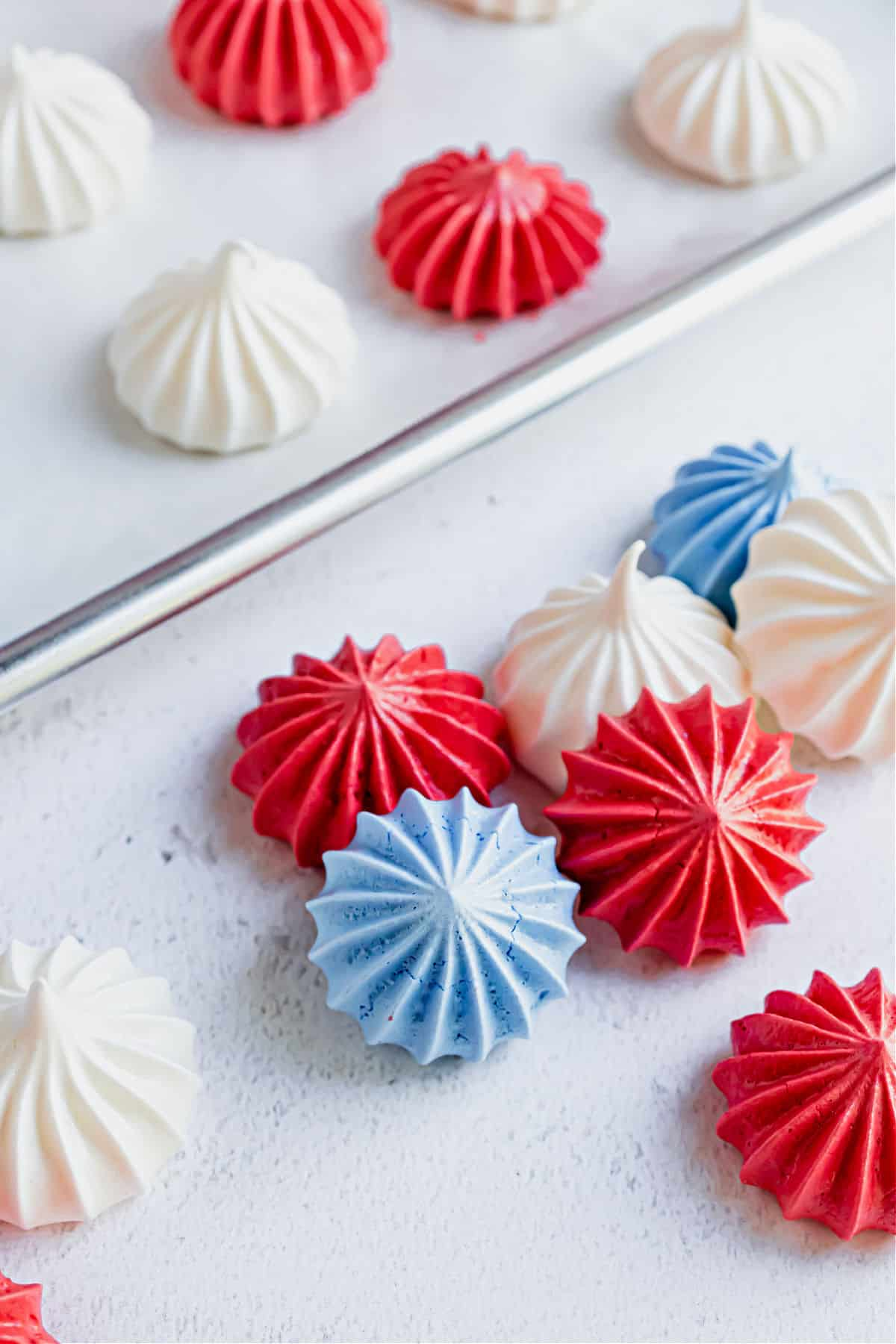 Meringue cookies with a 4th of july theme on baking sheet.