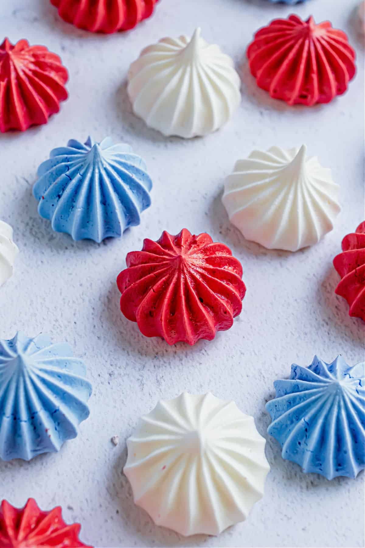 Red white and blue meringue cookies on parchment paper.