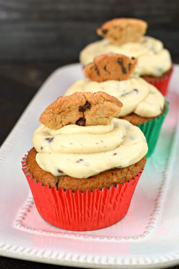 Three Chocolate chip cupcakes with cookie dough frosting on a rectangular plate, topped with a cookie