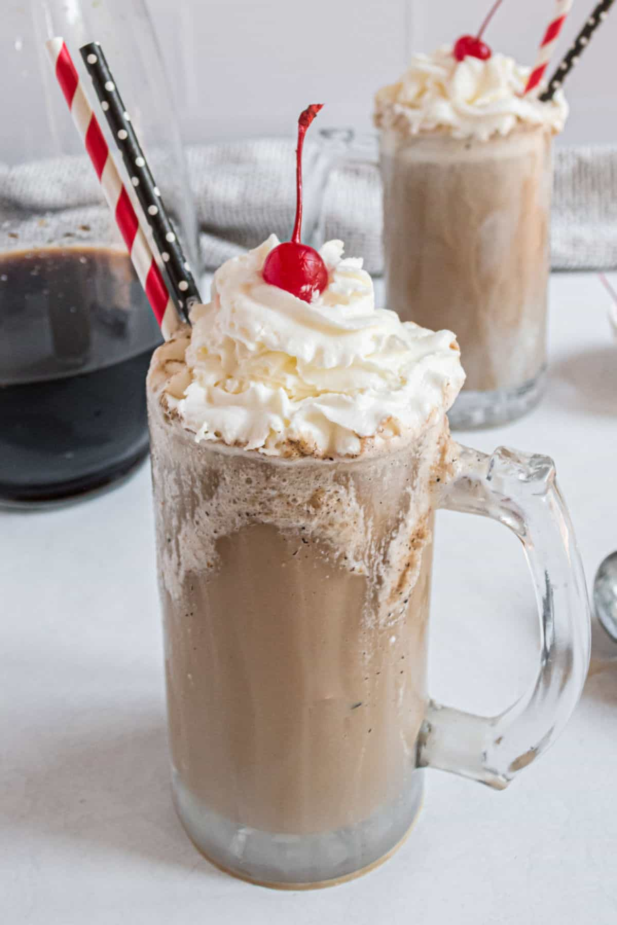 Homemade root beer with vanilla ice cream topped with whipped cream and cherry.
