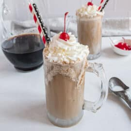 Homemade root beer float with whipped cream and a cherry.
